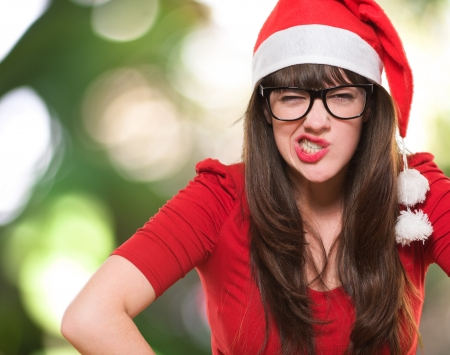 angry christmas woman wearing glasses against a nature background