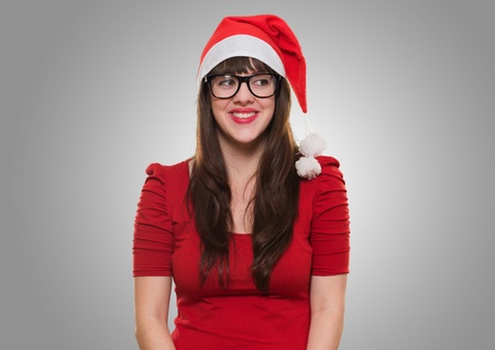 happy christmas woman wearing glasses and looking to a side against a grey background Stock Photo - 16290918