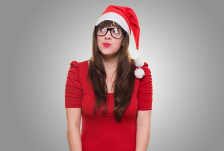 christmas woman wearing glasses and looking up against a grey background photo
