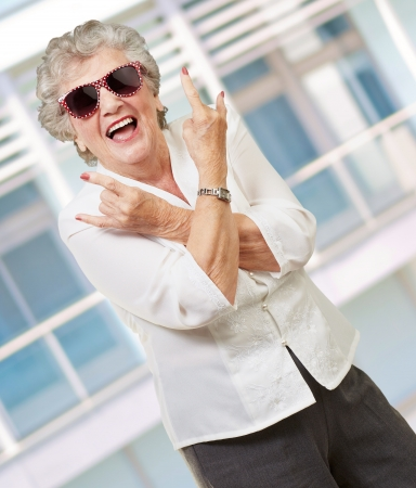 seniority: Senior woman wearing sunglasses doing funky action, outdoor Stock Photo