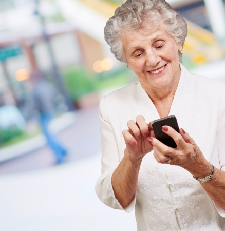 Senior woman with mobile phone, outdoor photo