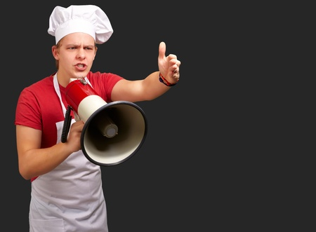 Portrait Of A Young Man With Megaphone On Black Background photo