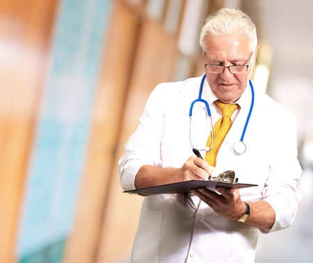 Senior Male Doctor Writing On Clipboard, Indoor photo