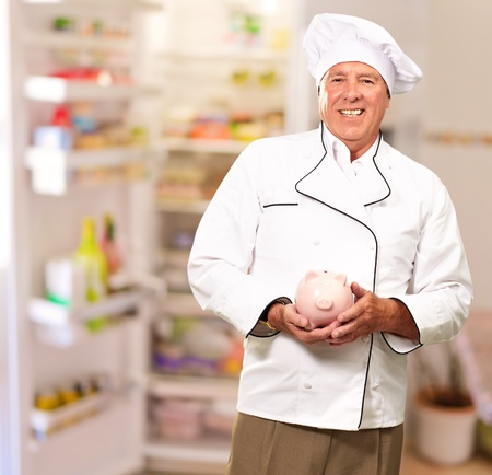 Portrait Of A Chef Holding Piggy Bank, Indoor photo