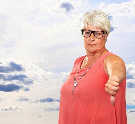 Senior Woman With Thumbs Down, Indoor Stock Photo - 16290460