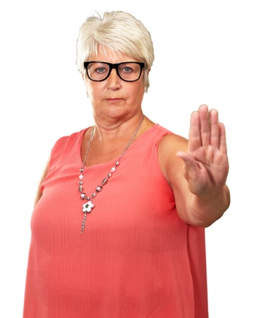 portrait of a senior woman showing stop sign on white background