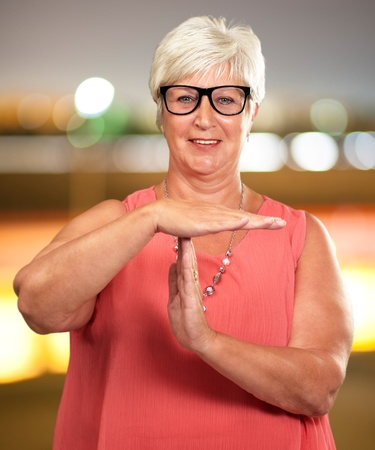 stop gesture: Portrait Of A Senior Woman Showing Time Out Signal, Background Stock Photo