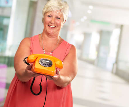 Portrait Of A Senior Woman Holding A Retro Phone On Wall Paper photo
