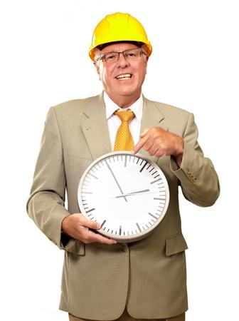 punctual: Retrato de un hombre mayor que sostiene un reloj de pared en el fondo blanco
