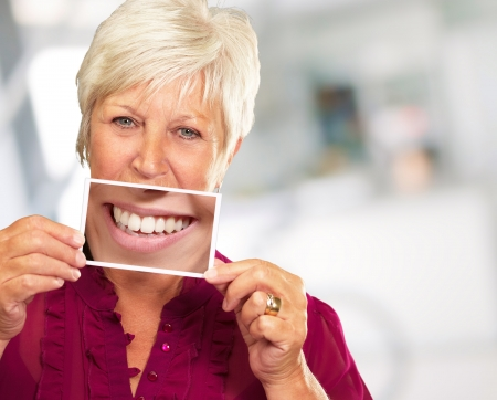 Senior Woman With Manifying Glass Showing Teeth, Background photo