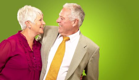 Portrait Of A Happy Senior Couple On Green Background photo