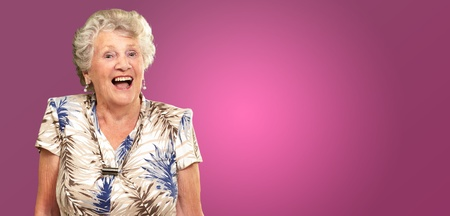 Portrait Of A Senior Woman Happy On Pink Background photo