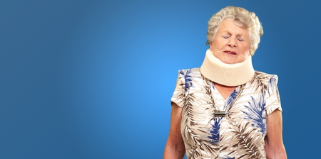 A Senior Woman Wearing A Neckbrace On Blue Background photo
