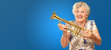 Portrait Of A Senior Woman Holding A Trumpet On Blue Background photo