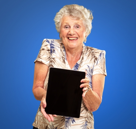 Portrait Of A Senior Woman Holding A Digital Tablet On Blue Background photo
