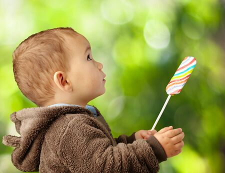 Portrait Of A Baby Holding Lollipop against a nature background photo
