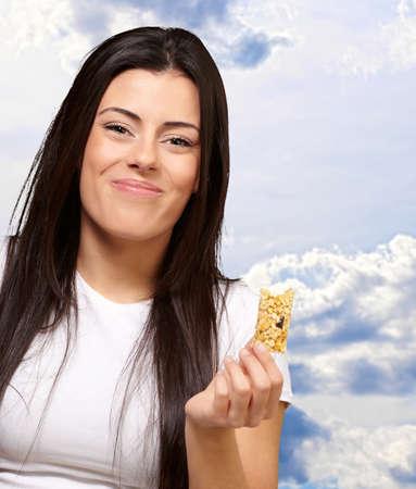 barra de cereal: Mujer comiendo una barra de cereal, al aire libre Foto de archivo