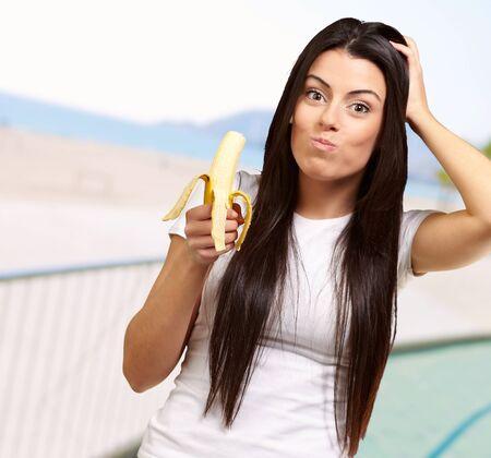 comiendo platano: Una mujer joven que come un plátano al aire libre, Foto de archivo