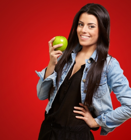 causal clothing: Woman Holding Green Apple Isolated On Red Background