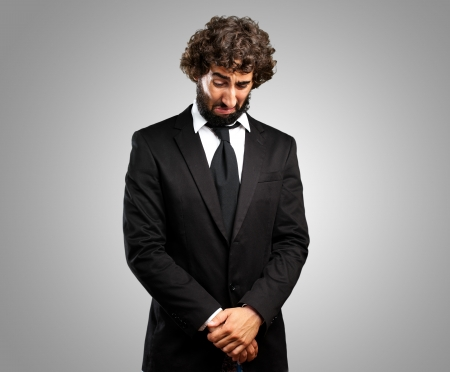 Portrait Of An Unhappy Businessman against a grey background Stock Photo - 16690482