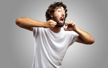 shaver: Man Cutting Beard against a grey background