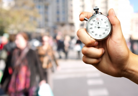 Close Up Of Hand Holding Stopwatch against a street background