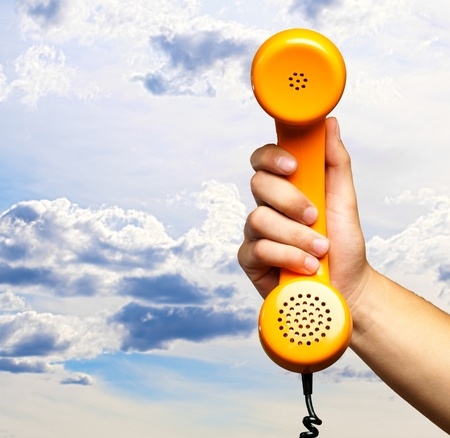 antique phone: Close Up Of Hand Holding Telephone against a cloudy sky background Stock Photo
