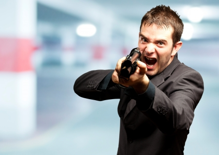 gun room: Angry Man Holding Gun in a garage Stock Photo