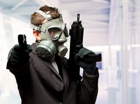 Businessman Holding Gun With Gas Mask against an abstract background photo