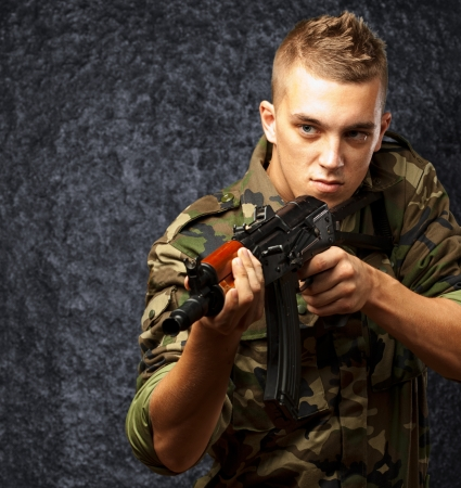 Portrait Of A Soldier Aiming With Gun against a grunge background Stock Photo - 16690564