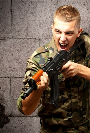 Portrait of an angry soldier aiming against a grunge background Stock Photo - 16690545