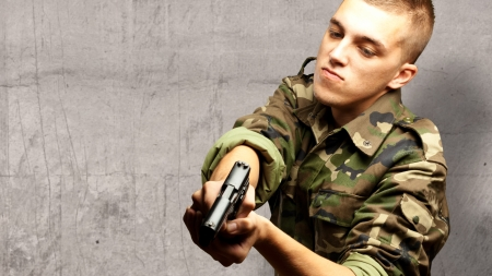 portrait of a serious soldier aiming against a concrete background Stock Photo - 16690561