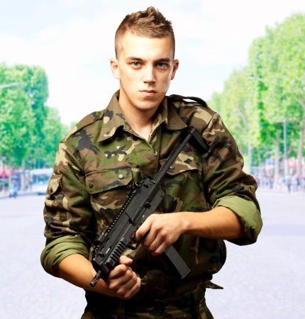 handsome soldier holding gun, outdoor photo