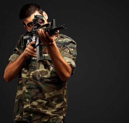 Soldier Gunman Aiming His Target On black Background photo