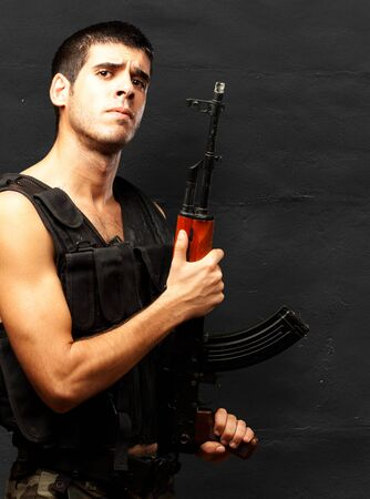 Portrait Of Soldier Holding Gun against a grunge background photo
