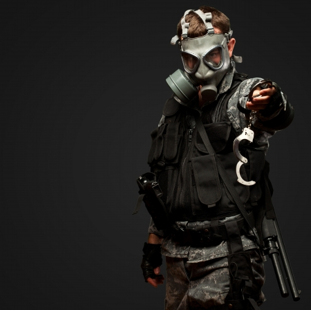 prisoner of war: Soldier With  A Gas Mask Holding Handcuffs against a black background Stock Photo
