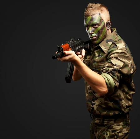 Portrait Of A Soldier Aiming With Gun against a black background Stock Photo - 16690571