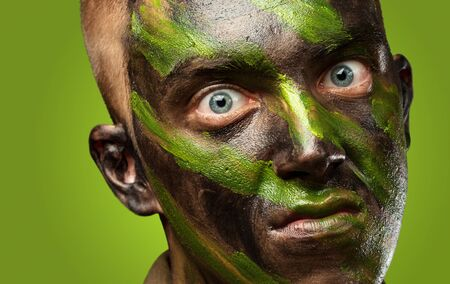 closeup of angry soldier with painting against a green background Stock Photo - 16690575