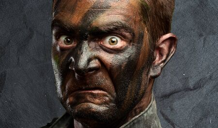 Close Up Of Angry Soldier Face against a grunge background photo