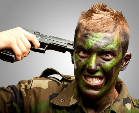 kill: Soldier Putting Gunshot On Head against a grey background Stock Photo