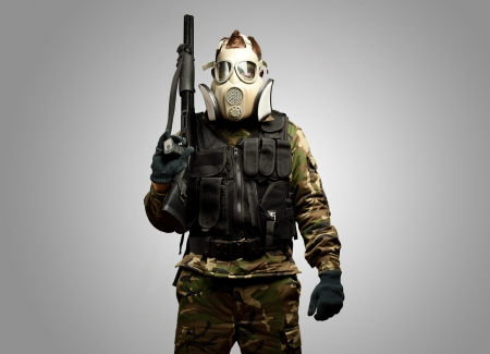 Portrait Of A Soldier With Gas Mask against a grey background Stock Photo
