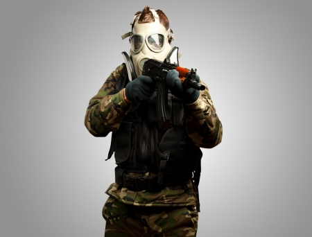 Portrait Of A Soldier With Gas Mask Aiming With Gun against a grey background photo