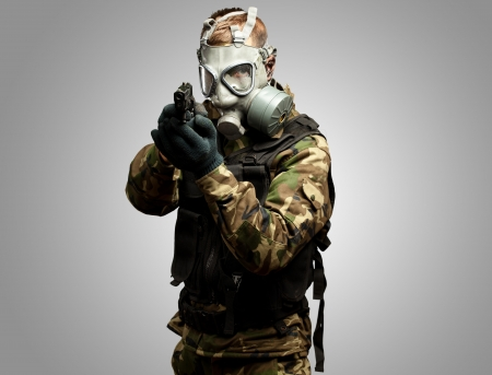 war crimes: Portrait Of A Soldier With Gas Mask Aiming With Gun against a grey background