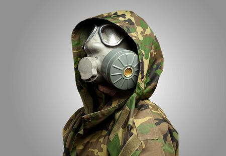 gas mask: closeup of a soldier wearing a gas mask against a grey background Stock Photo