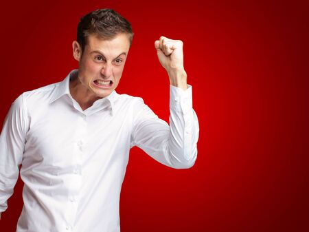angry man: Portrait Of Angry Young Man Clenching His Fist On Red Background Stock Photo