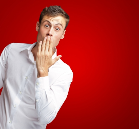 Portrait Of Young Man Covering His Mouth With Hand On Red Background Stock Photo - 16681913