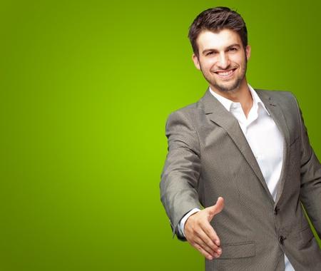 personas saludandose: Retrato De Joven Empresario En Un Juego tiende la mano para un apret�n de manos en fondo verde