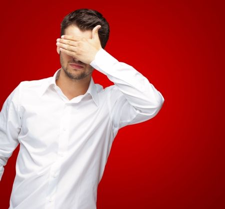 unsighted: Portrait Of An Businessman Covering Eyes Isolated On Red Background