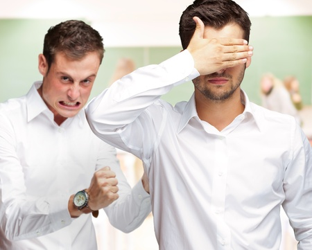 unsighted: Young Man Covering Eyes And Aggressive Man Standing Behind, Indoors Stock Photo