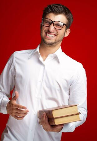 Portrait Of A Student Holding Book Isolated On Red Background Stock Photo - 16690611